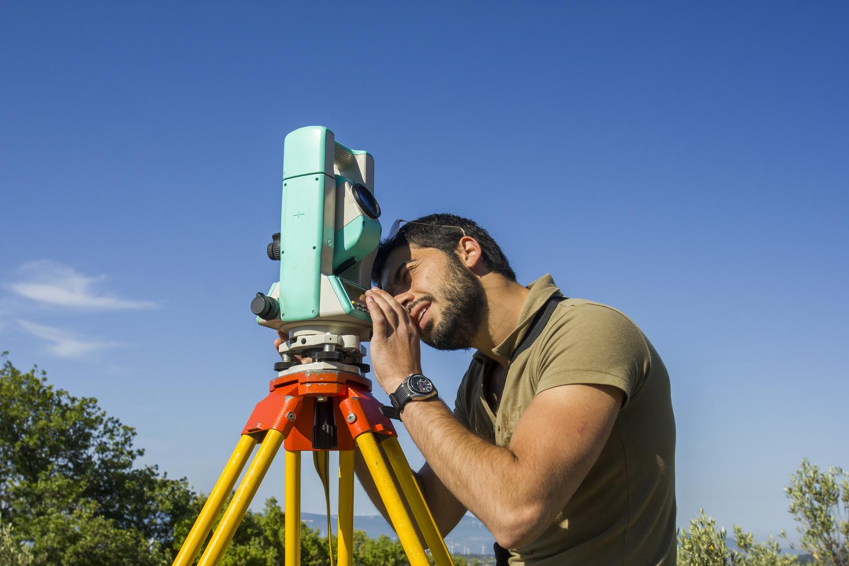 photo d'un géomètre réalisant des mesures