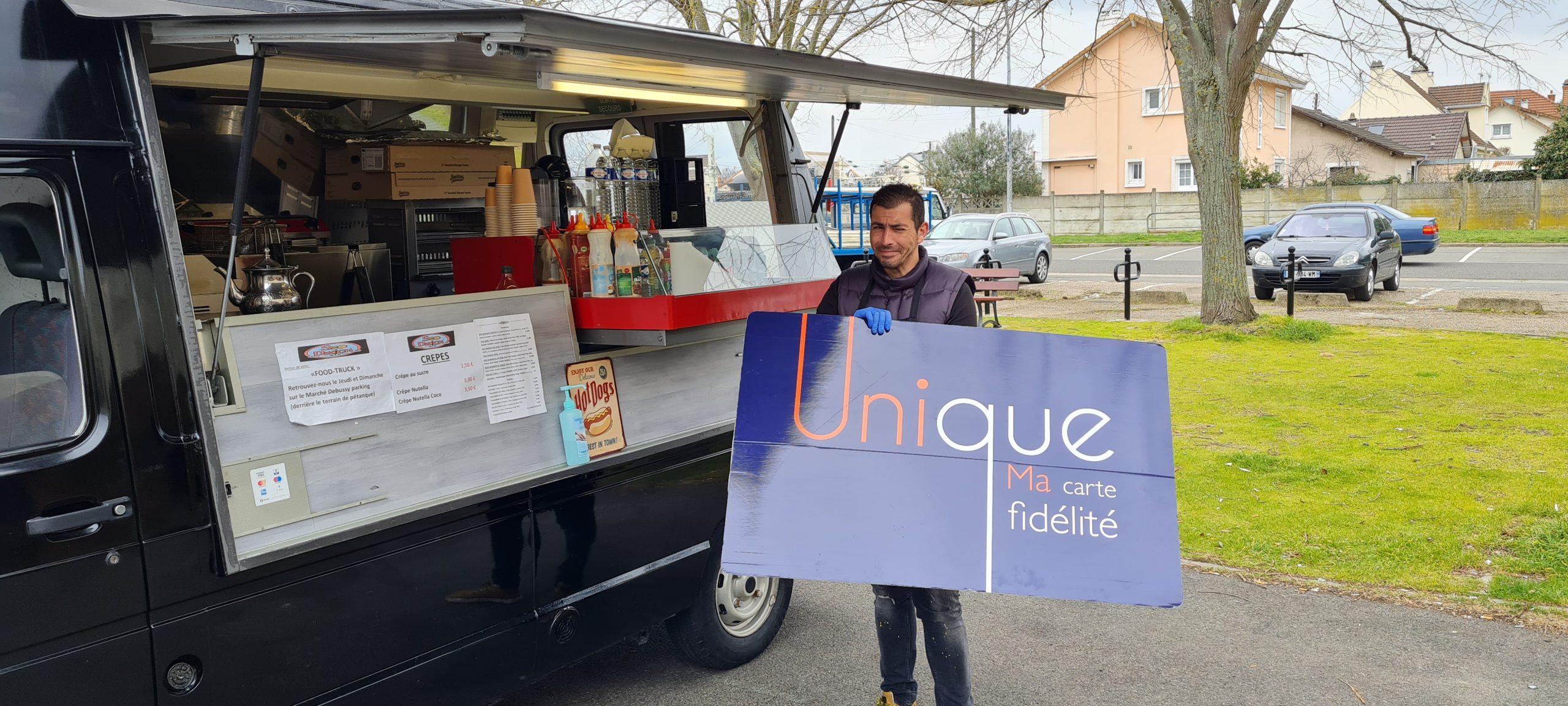 photo de zizou propriétaire du food truck du marché Debussy à Sartrouville devant son camion qui tient sa carte unique programme de fidélité de la ville de Sartrouville